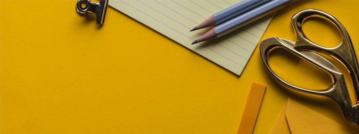 popierius ir įrankiai geltoname fone